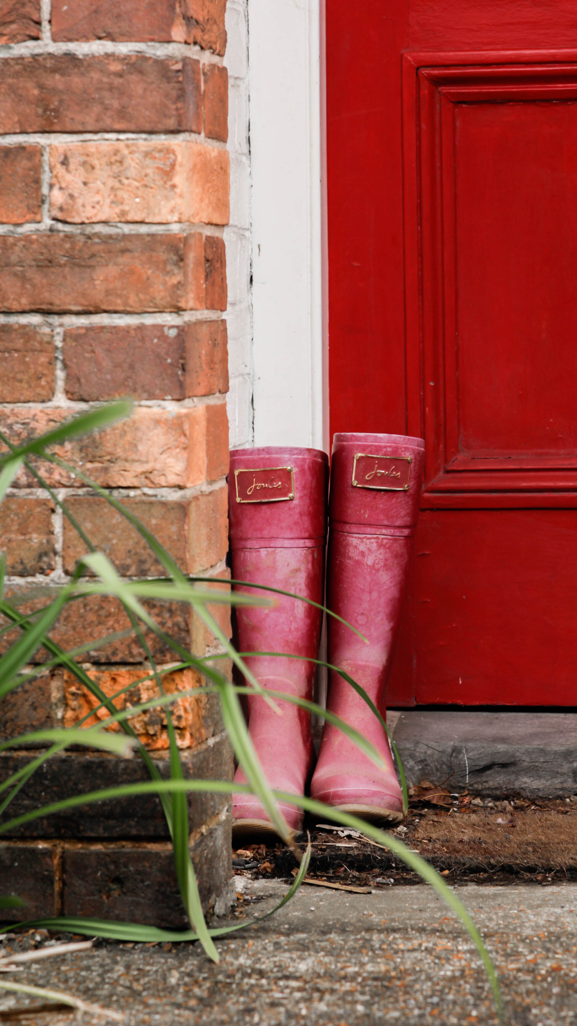 Rain boots placed outside by a red door in the countryside of England during autumn
